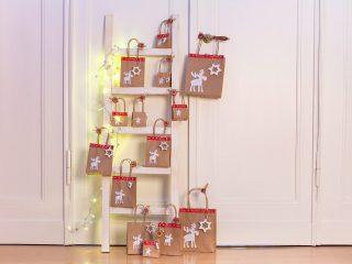 Adventskalender aus Tüten an einer Leiter befestigt